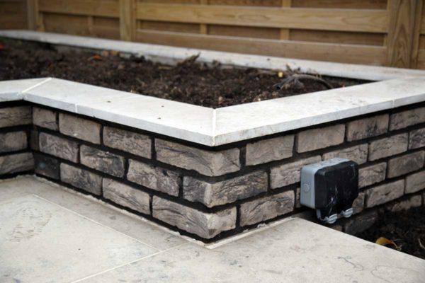 Grey brick raised planter in Forest Gate
